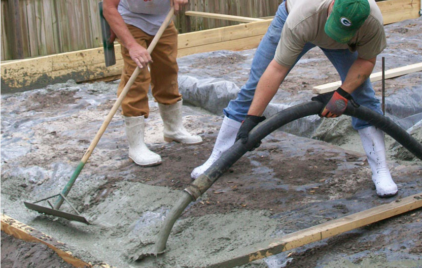 One of the first stages of building the addition was pouring the foundation. Here you can see two of our construction workers spreading the wet cement through a hose and and using another tool for spreading it around evenly.